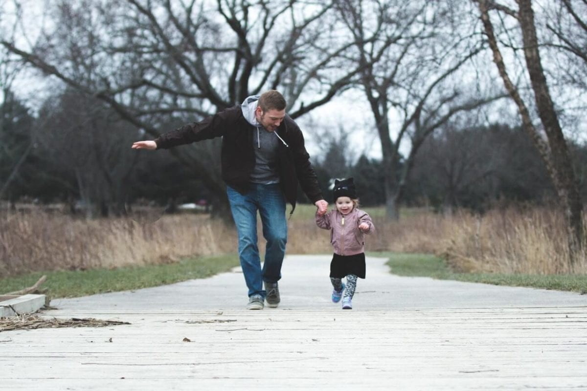 Father and daughter healthy running outdoors co-parenting