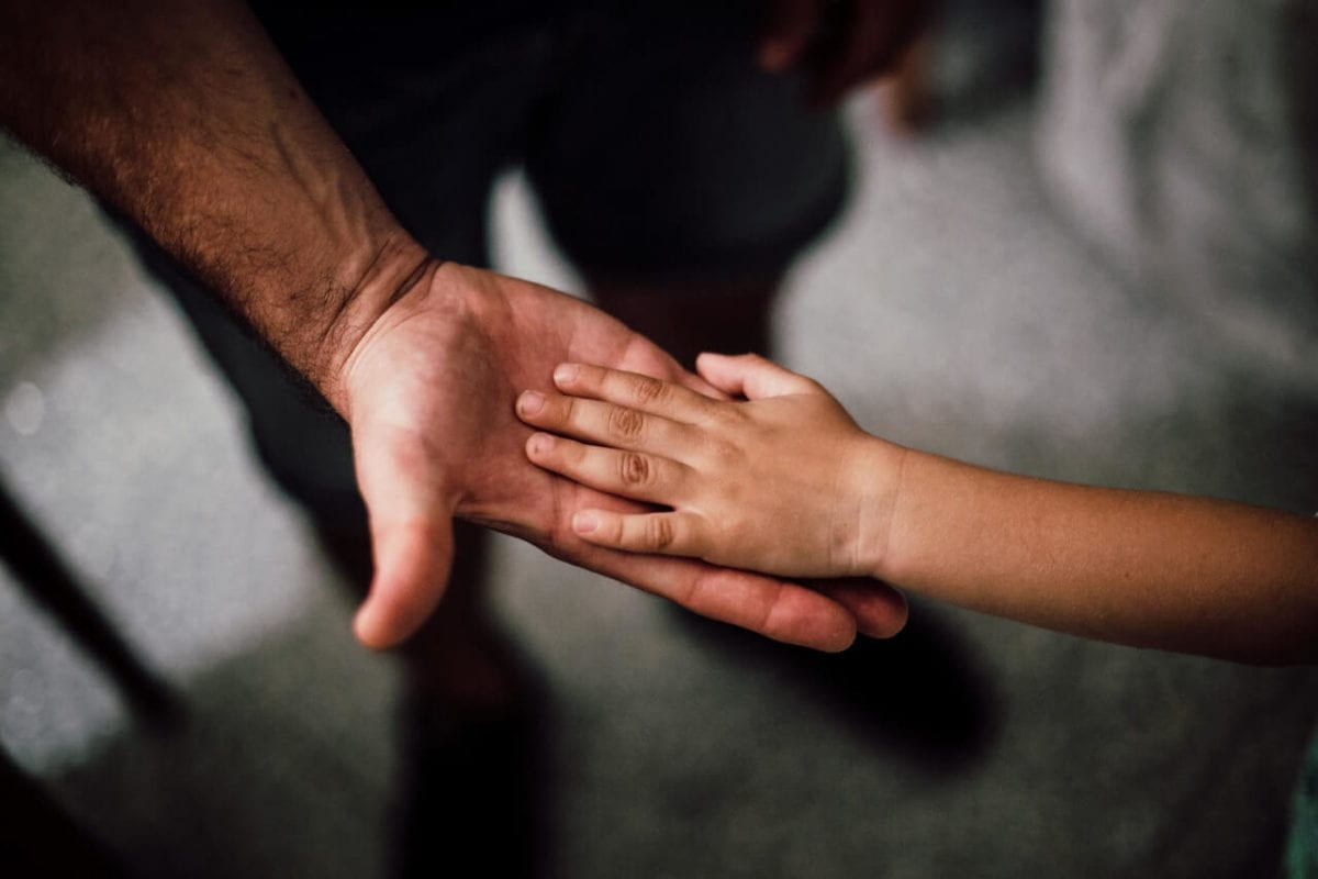 Parent and child support payments holding hands