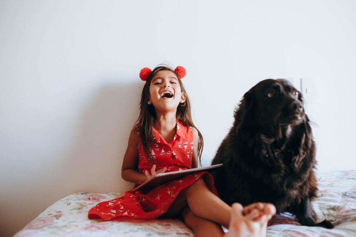 Young girl laughing with happiness next to pet dog custody