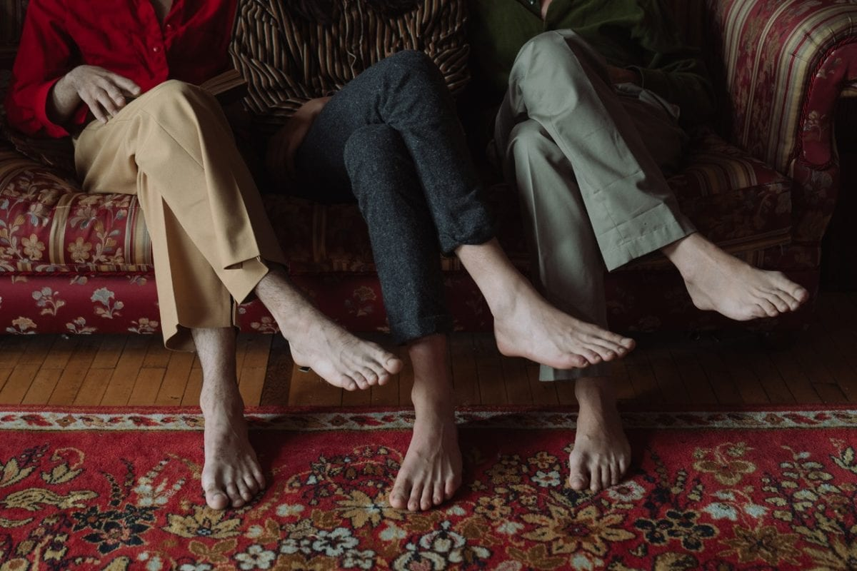 Three pairs of feet side by side implying throuple relationships