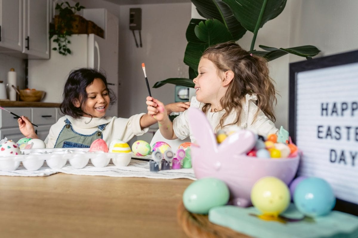 two young girls painting Easter eggs in the kitchen with child custody during school holidays issues resolved