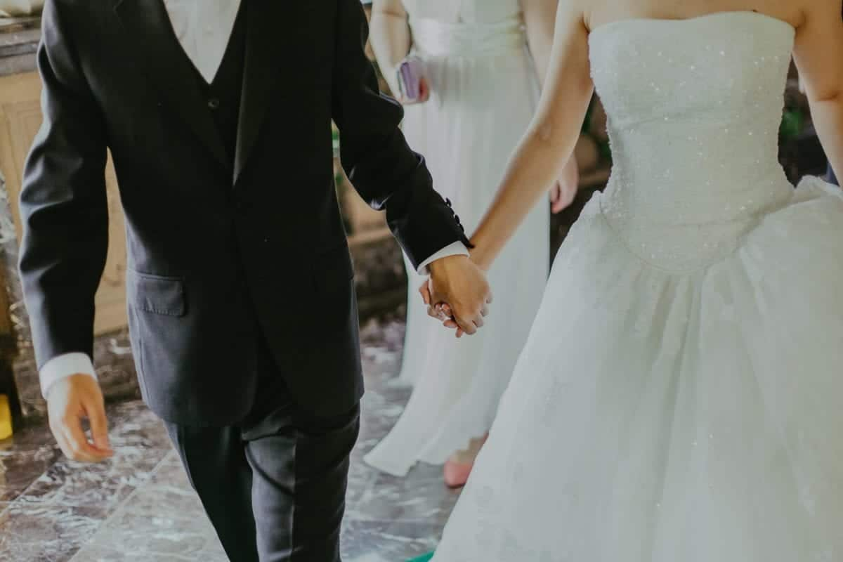 Bride and groom holding hands after signing a binding financial agreement