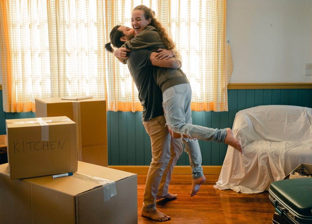 Happy couple with prenup benefits unpacking boxes in new home